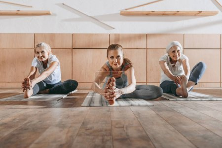 Photo for Group of women stretching on yoga mats in studio - Royalty Free Image
