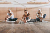 group of women stretching on yoga mats in studio