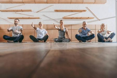 group of senior people with thumbs up in yoga studio