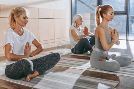 Photo pour Groupe de femmes méditant dans lotus yoga pose avec mudra namaste - image libre de droit