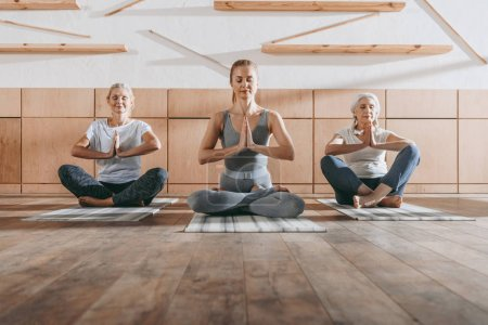 group of women meditating in lotus yoga pose with namaste mudra