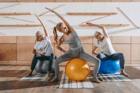 Foto de Grupo de mujeres hacer ejercicio con pelotas de gimnasio en studio - Imagen libre de derechos