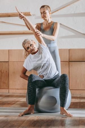 Foto de Senior femenino y el entrenador haciendo ejercicio en pelotas fitness en estudio - Imagen libre de derechos