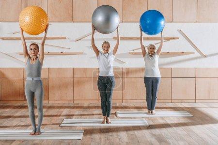 Foto de Grupo de personas mayores hacer ejercicio con pelotas de gimnasio en studio - Imagen libre de derechos