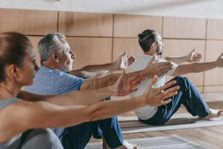 Photo for Group of people practicing yoga on mats in studio - Royalty Free Image