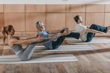 Photo for Female instructor exercising with mature men at training class - Royalty Free Image