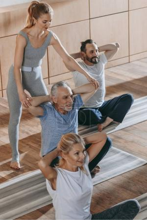 female instructor training senior people sitting on yoga mats in fitness studio