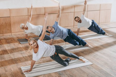 senior group of people with instructor exercising on yoga mats in fitness studio