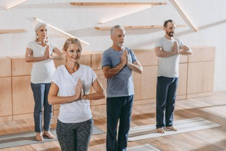 senior group of people with instructor practicing yoga at training class