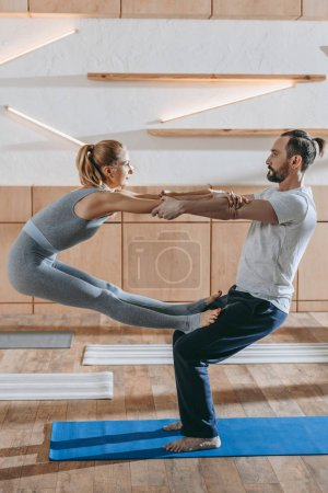 middle aged couple practicing yoga together in fitness studio
