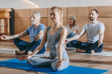 female instructor with senior people sitting in lotus position on yoga mats