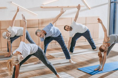 senior people with instructor exercising on yoga mats at training class