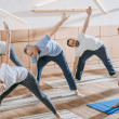 Senior people with instructor exercising on yoga m...