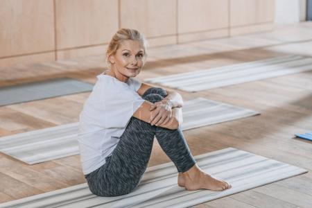 Foto de Hermosa mujer madura sentada en la estera de la yoga y sonriendo a la cámara en clase de formación - Imagen libre de derechos