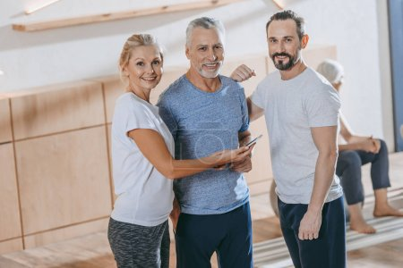 senior people using smartphone and smiling at camera in fitness studio