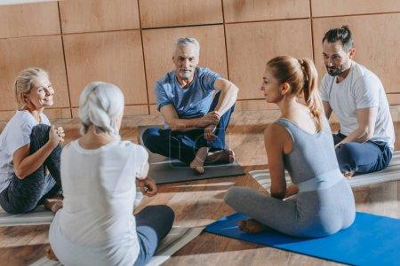 Photo pour Personnes âgées souriantes avec instructeur assis sur des tapis de yoga à la classe de formation - image libre de droit