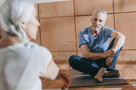selective focus on senior people in sportswear sitting on yoga mats at training class