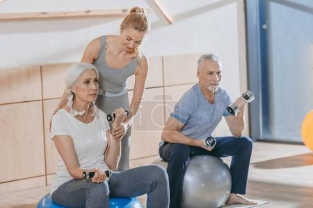 instructor helping senior people training with dumbbells and fitness balls in fitness studio