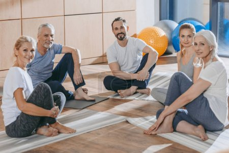 mature people with instructor sitting on yoga mats and looking at camera