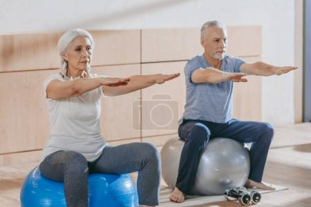 senior people exercising on fitness ball at training class