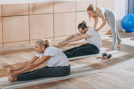 instructor helping mature people stretching on yoga mats at training class