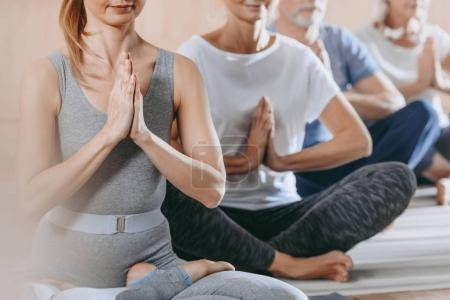 cropped shot of senior people with instructor sitting in lotus position on yoga mats