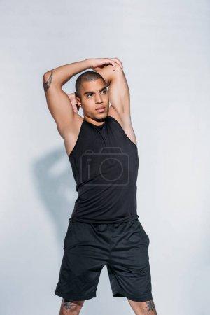 african american tattooed sportive man stretching body