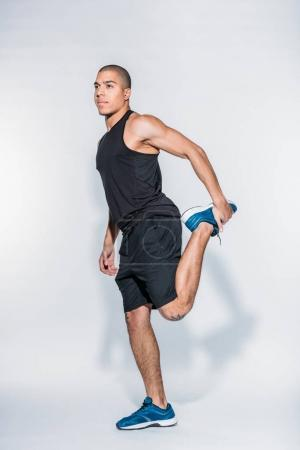 Photo for African american sportive man stretching legs - Royalty Free Image
