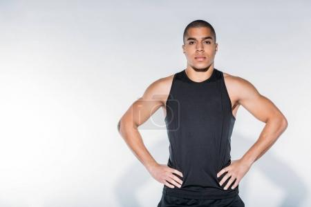 handsome african american sportive man standing and looking at camera