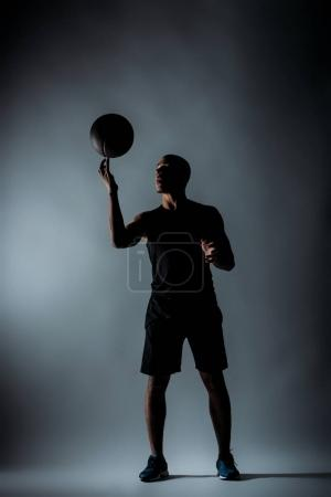 Photo for African american sportsman spinning basketball ball on finger in dark room - Royalty Free Image