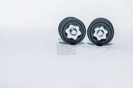 two black dumbbells on white floor