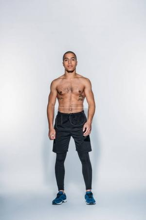 handsome african american sportsman standing and looking at camera