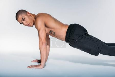 african american sportive man doing push up and looking at camera