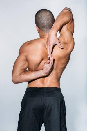 rear view of african american sportsman stretching back isolated on white