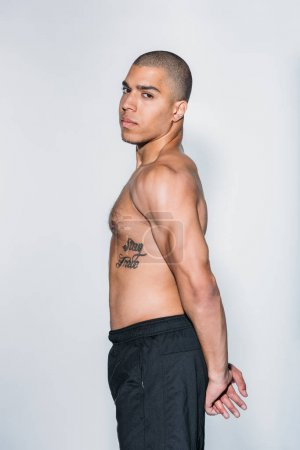side view of tattooed african american sportsman stretching isolated on white