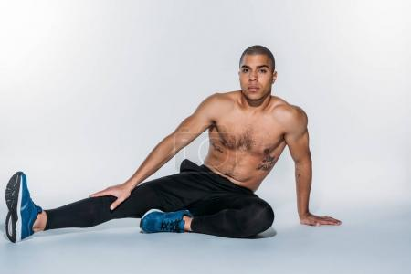 torso african american sportsman sitting on floor and stretching