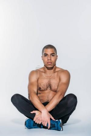 shirtless african american sportive man stretching legs on floor