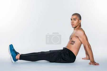 shirtless african american sportsman sitting on floor and looking at camera