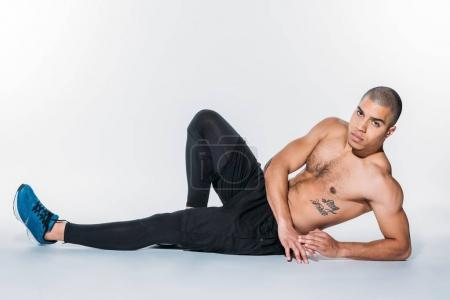 shirtless tattooed african american sportsman lying on floor and looking at camera