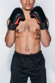 cropped image of tattooed african american boxer standing isolated on white