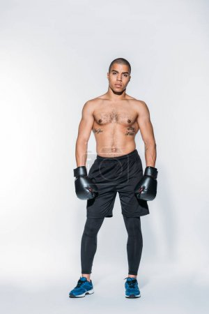 muscular african american boxer standing and looking at camera