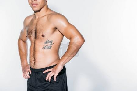 cropped image of tattooed african american sportsman standing on white