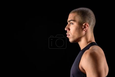 Photo for Side view of serious african american man standing isolated on black - Royalty Free Image