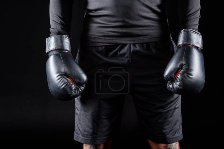 Photo for Cropped shot of boxer in black gloves isolated on black - Royalty Free Image