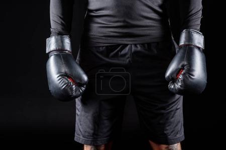 Photo pour Photo recadrée de boxer en gants noirs isolés sur fond noir - image libre de droit