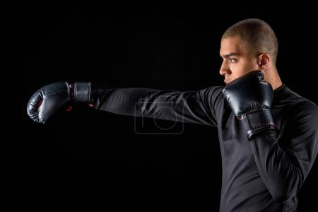 side view of african american boxer making hit isolated on black