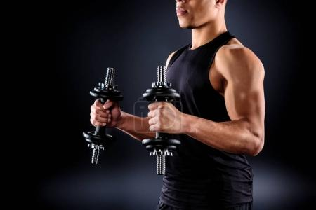 cropped shot of african american sportsman working out with dumbbells on black