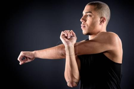 Photo for Young african american sportsman stretching arms on black - Royalty Free Image