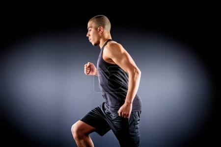 Photo for Side view of african american sportsman running on black - Royalty Free Image