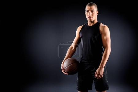 young african american basketball player with ball on black